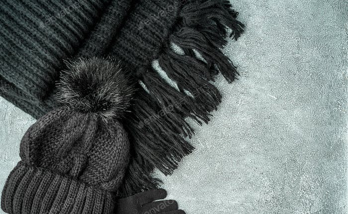Flat lay winter or autumn warm woman accessories - black knitted scarf, hat,