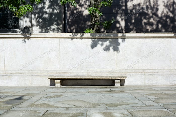 Empty stone bench with light stone background and tree leaves