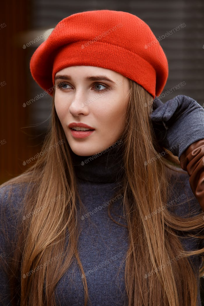 Stylish girl dressed in a gray turtleneck and orange beret poses outside