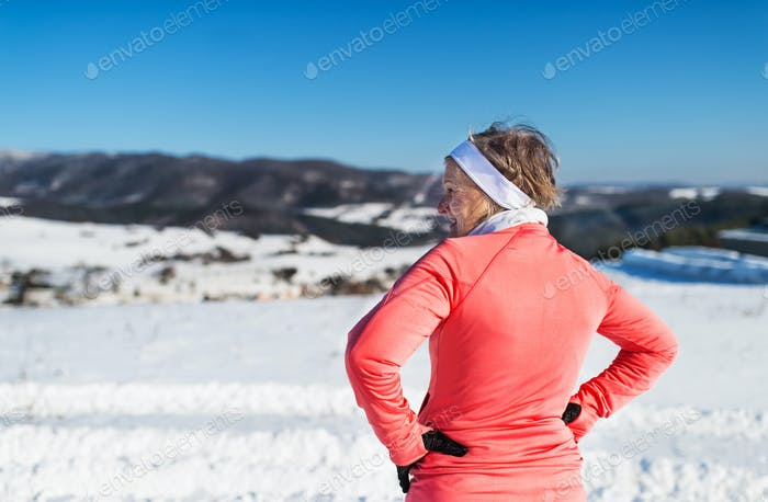 Rear view of senior woman runner resting in winter nature, arms on hips.