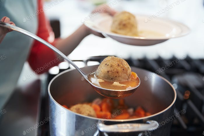 Woman serving Jewish matzon ball soup from a pot, close up