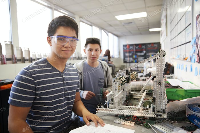 Portrait Of Two Male College Students Building Machine In Science Robotics Or Engineering Class