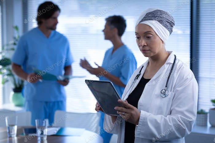 Matured mixed race female doctor looking at digital tablet in clinic at hospital.