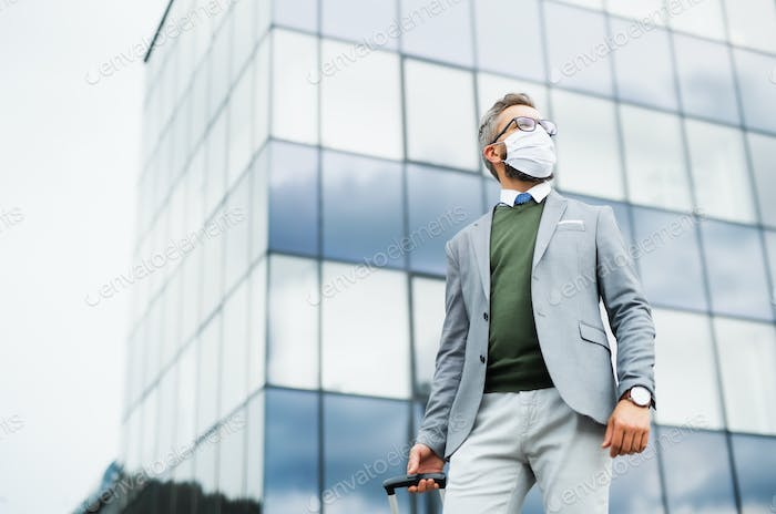 Businessman with luggage going on business trip, wearing face mask at the airport