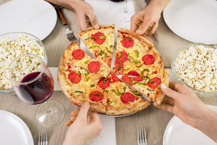 Hands of young friends taking slices of appetizing pizza while having lunch