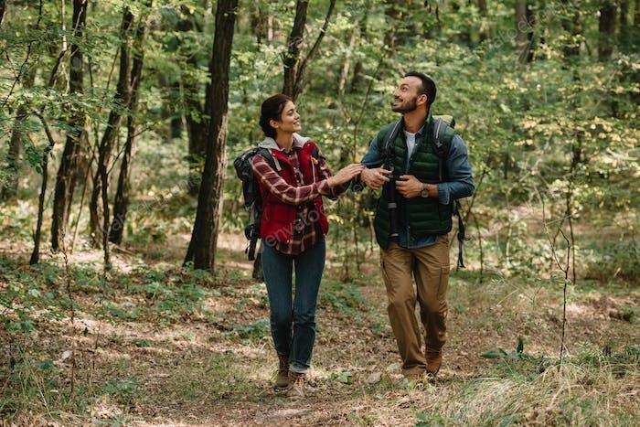 pareja de viajeros con mochilas de senderismo en el bosque