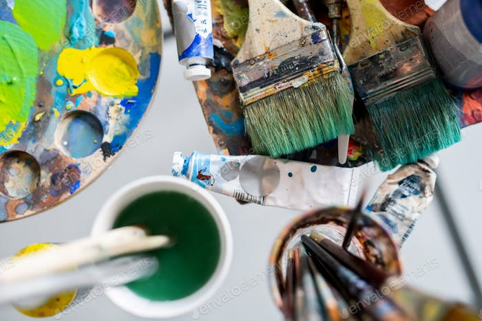 Paintbrushes on table and in glasses, oil paints and palette