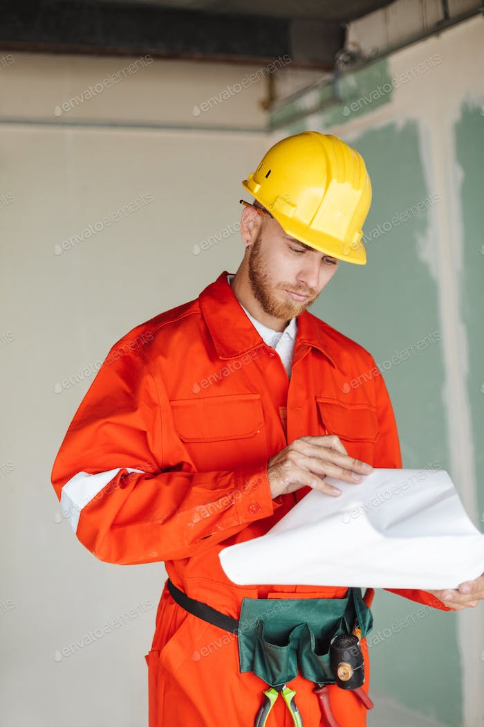 Young foreman in orange work clothes and yellow hardhat thoughtf