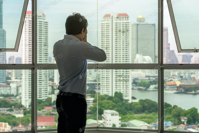 depressed man standing face in hands on the interior Skyscraper with low light environment