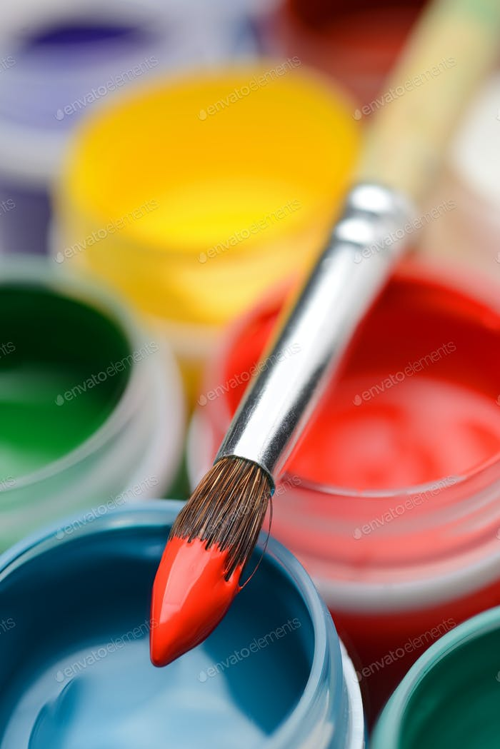 Gouache paint jars and paintbrush