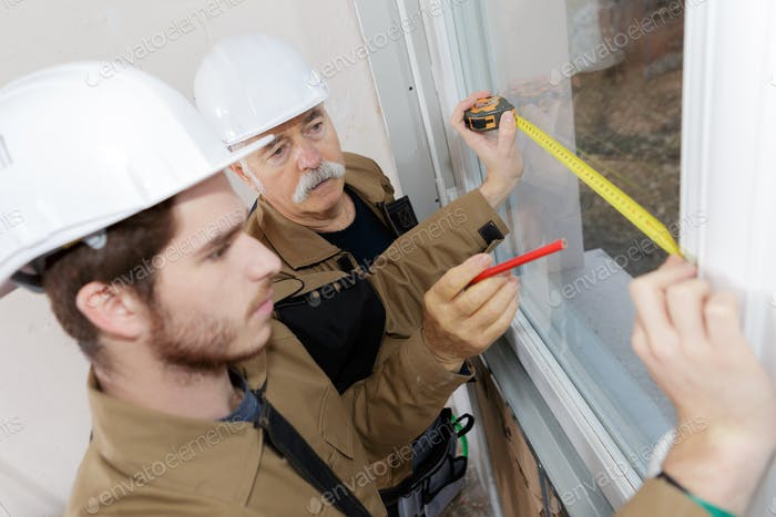 Men measuring windows