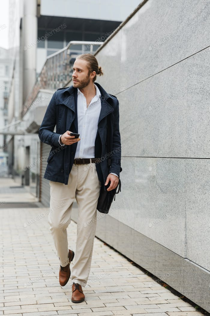 Attractive young bearded businessman walking outdoors