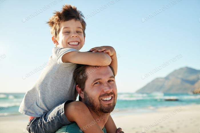 Hombre blanco adulto medio en una Playa con hijo de cuatro Año en sus hombros, mirando a la cámara, de cerca