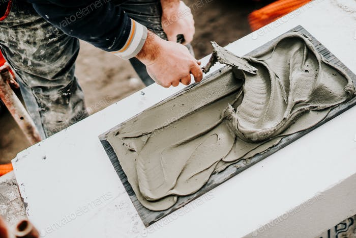 Details of worker using trowel and mortar for stone installation