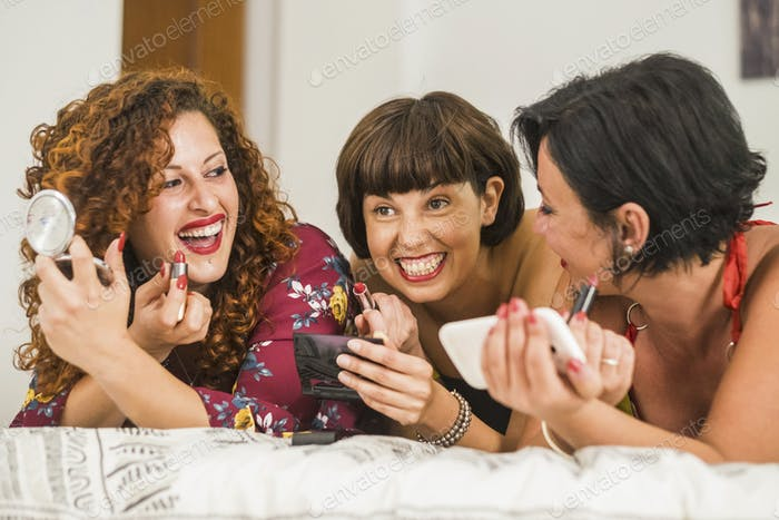 Three cheerful young women at home getting ready with red lipstick make up lay down on the bed