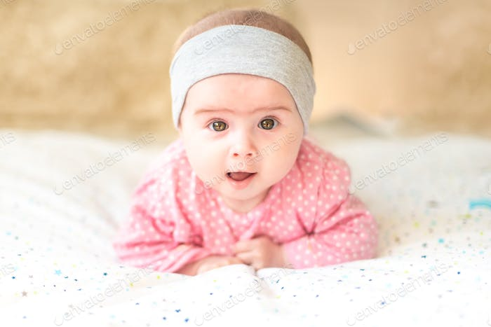 Adorable baby girl with grey headband looking towards camera and smiling. Health concept