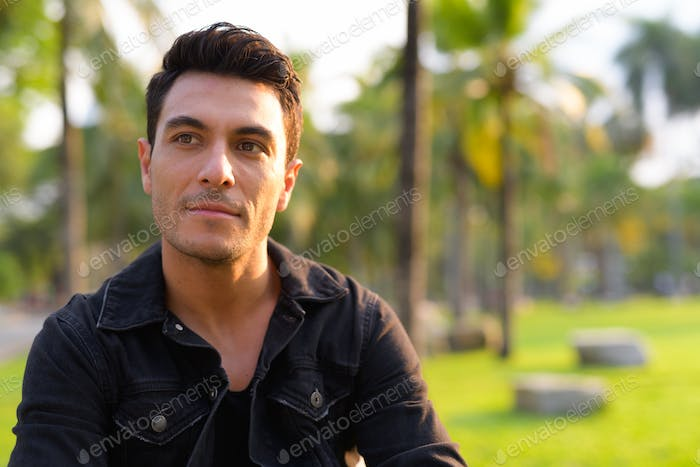 Face of young handsome Hispanic man thinking in the park