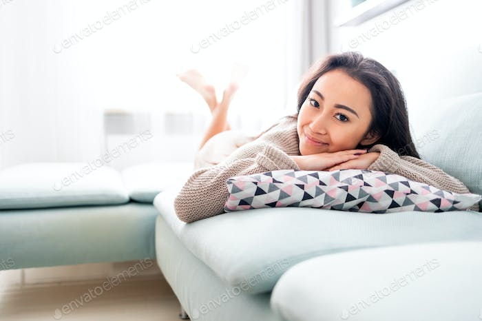 Happy asian girl lying on sofa with pillow at home
