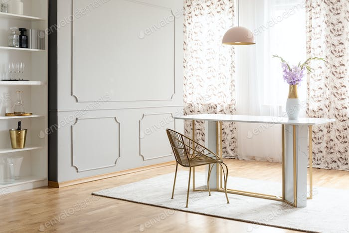 Real photo of a glamour dining room interior with a table, chair