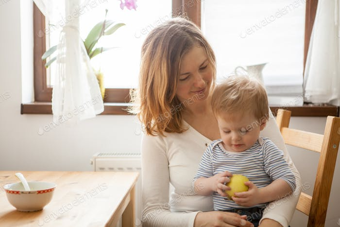 Thumbnail for Baby boy in hands of her mother eating an apple