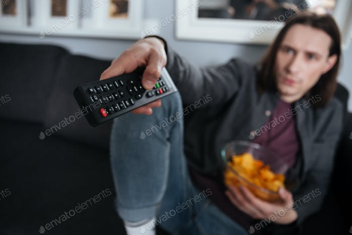 Young man sitting at home indoors. Focus on remote control.