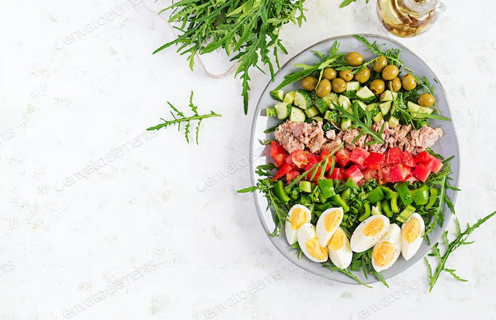 una fish salad with eggs, cucumber, tomatoes, olives and arugula