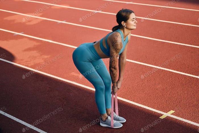 Attractive girl in stylish sportswear stretching with rubber band during workout on city stadium