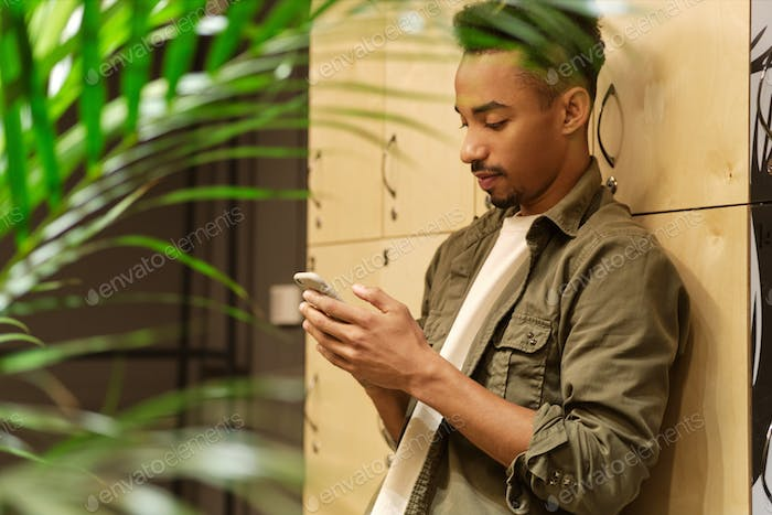 Side view of young casual African American guy thoughtfully using cellphone in locker room