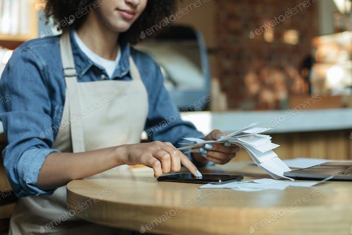 Ocupado afroamericano joven propietario en delantal trabaja con papeles, cuenta costos y ganancias en