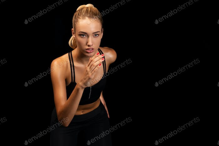 Young Woman Running In Place Over Black Background In Studio