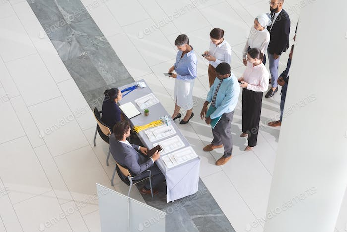 High angle view diverse business people checking in at conference registration table in office