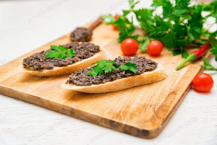Fresh tasty bruschetta with truffle sauce, parsley and tomates