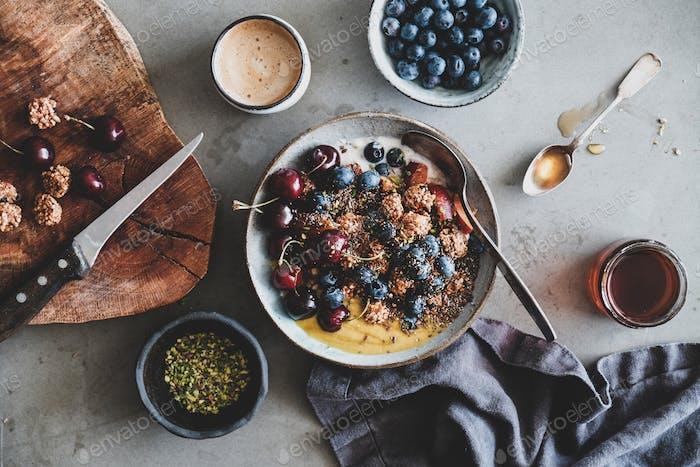 Quinoa Hafermüsli mit Früchten, Honig und Tasse Kaffee