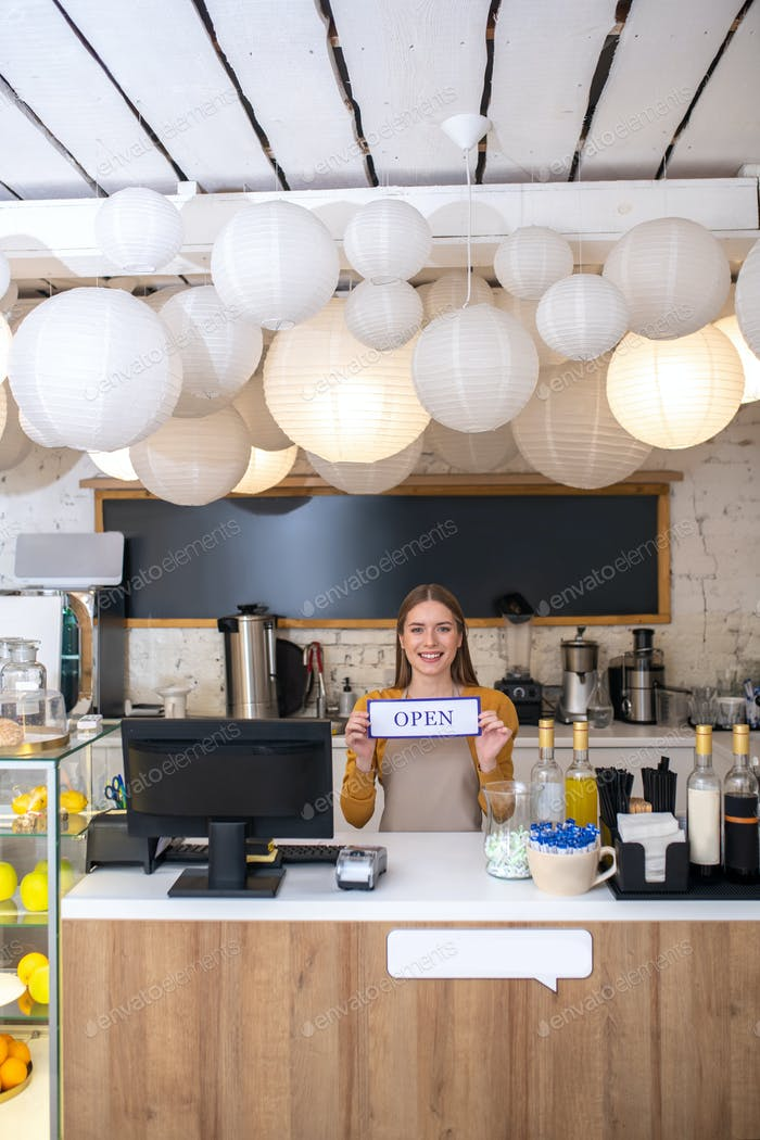 Smiling young woman opening a new coffee shop