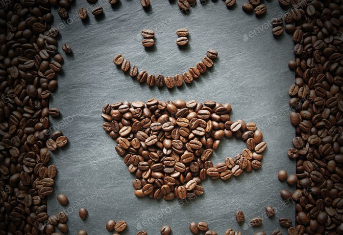 Smiley face from coffee beans at stone background