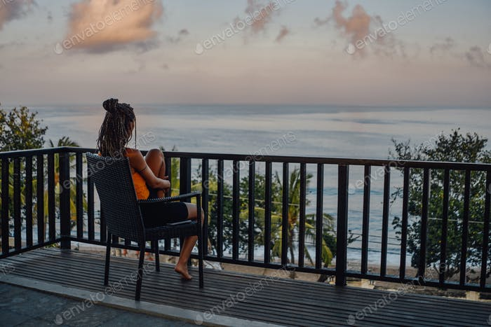 Carefree woman sitting on chair against beach landscape