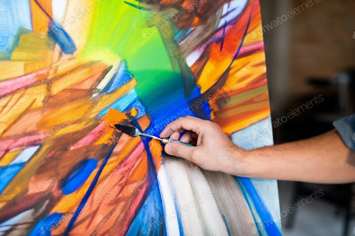 Hand of contemporary painter with special instrument mixing colors on paper