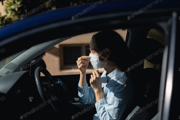Kaukasische Frau sitzt in einem Auto trägt coronavirus covid19 Maske