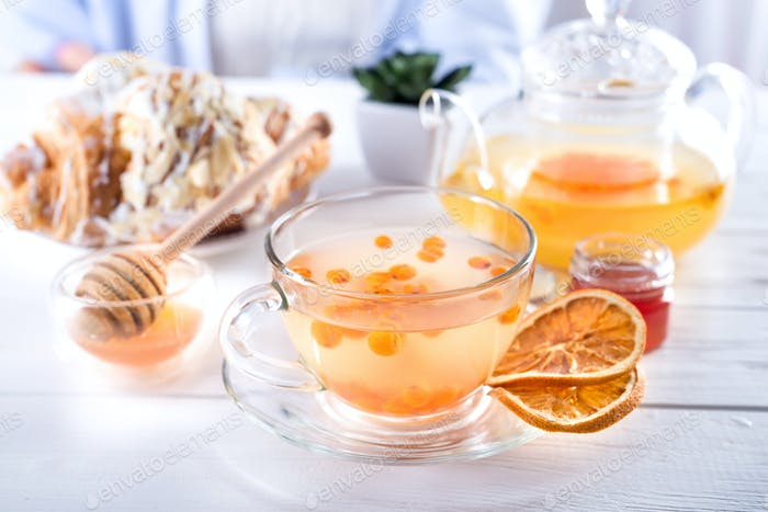 Vitaminic healthy sea buckthorn tea in small glass tea pot with sea buckthorn berries