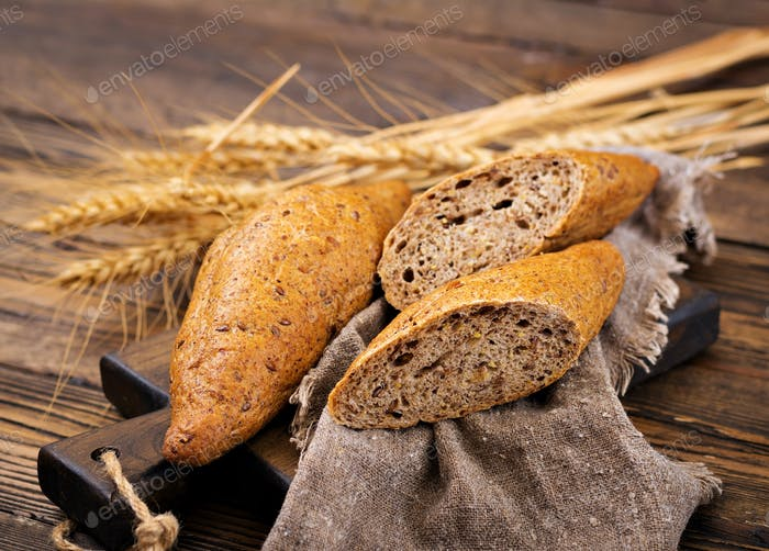 Buns of whole-grain flour with the addition of flax seeds on a wooden background.