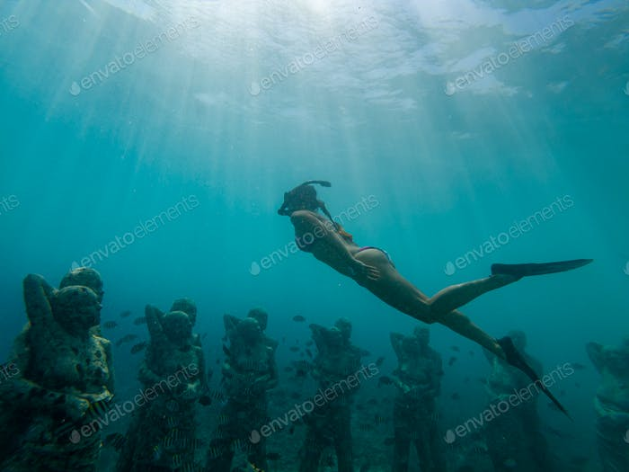 Freediving Girl swims over Underwater sculptures gili Meno, Southeast Asia