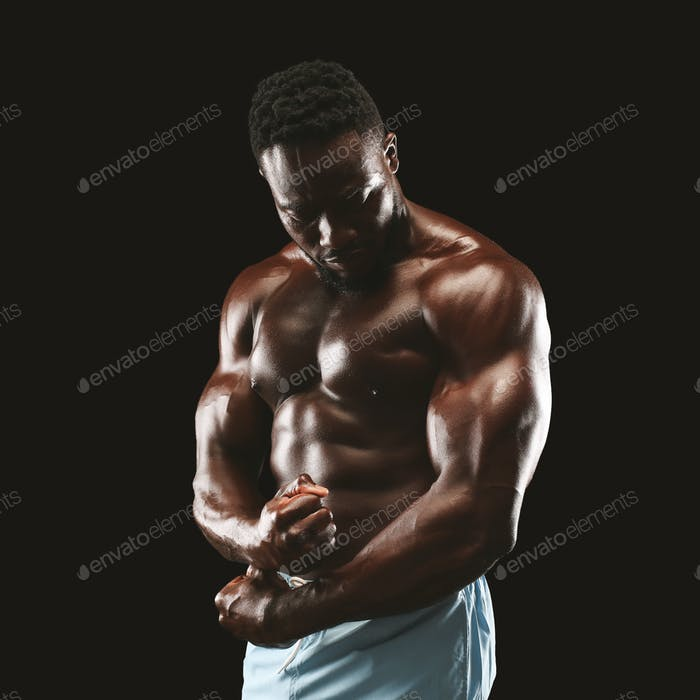 Portrait of black fitness model demonstrating side chest pose