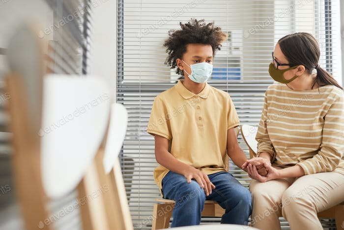 Anxious Teenage Boy Wearing Mask in Line at Hospital