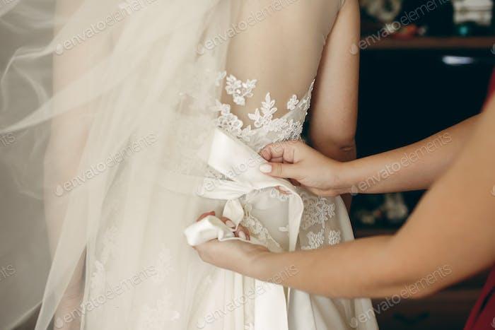 Beautiful brunette bride putting on wedding dress