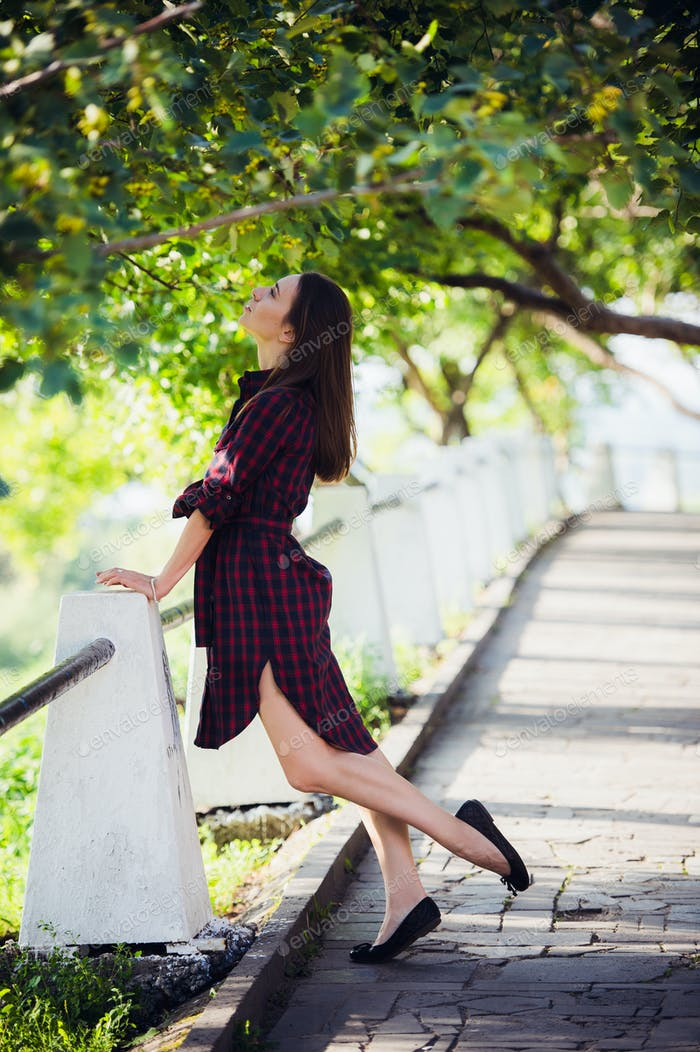 Beautiful, pretty woman in casual checkered dress walking at park outdoors. Street fashion style.
