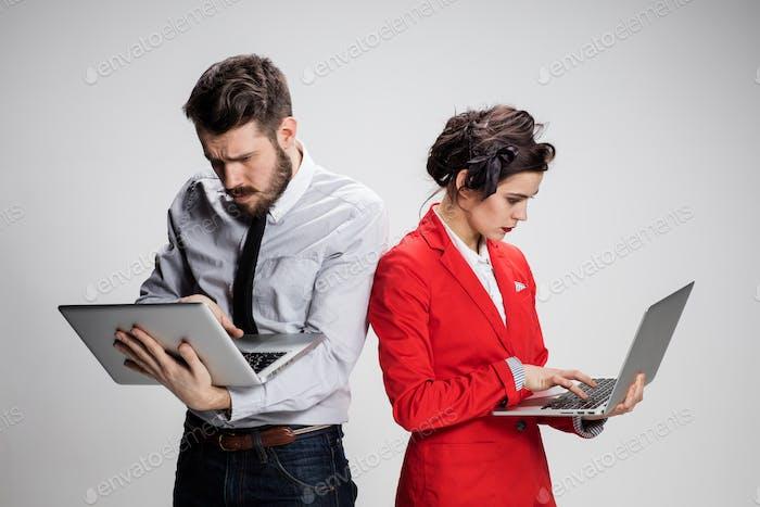 Молодой бизнесмен и бизнесмен с ноутбуками общается на сером фоне
