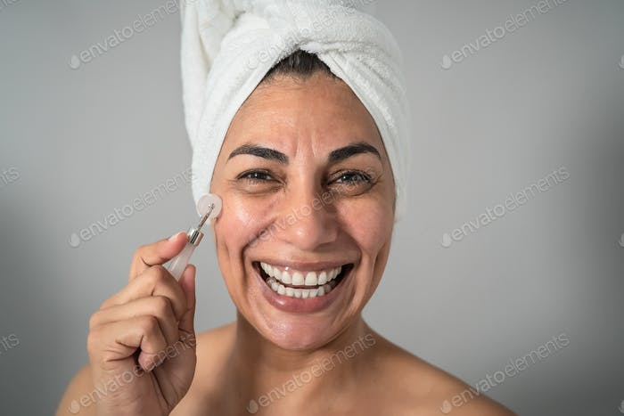 Happy Latin mature woman having skin care spa day - People wellness lifestyle concept
