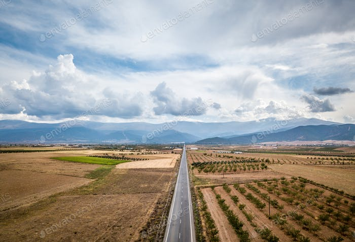 Aerial View Of Straight Tarred Road Through Guadix, Granada. In the background Sierra Nevada