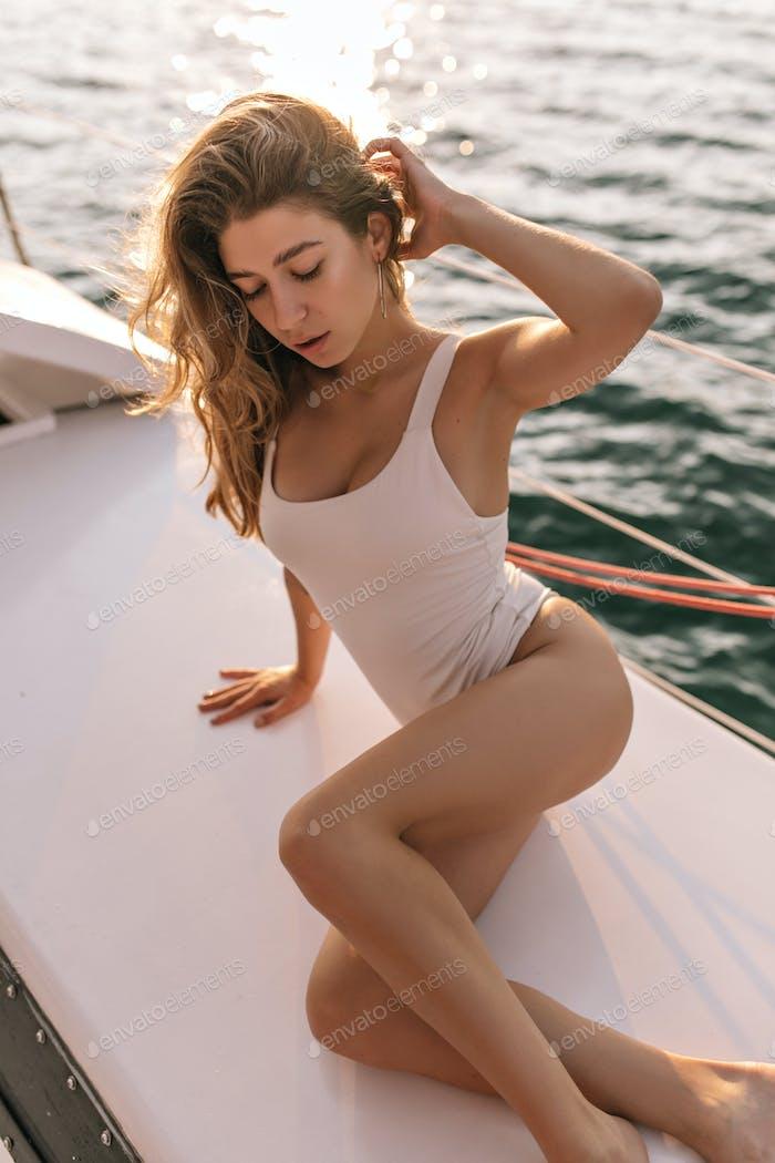 Gut gebaute junge Blondine mit langen, flauschigen Haaren im weißen Badeanzug posiert auf der Yacht und schaut nach unten