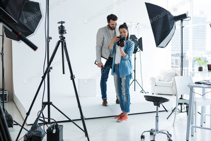 Photographer and male model reviewing captured photos in digital camera
